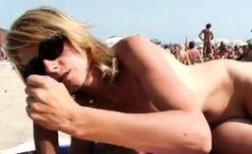 Nudist couple engaging in sloppy oral sex right on the beach