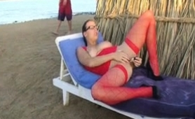 buxom-babe-in-sexy-red-lingerie-masturbates-on-the-beach